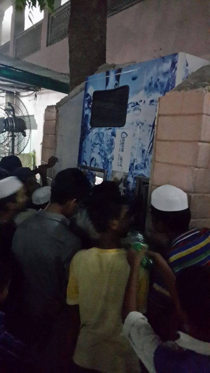 Children lining up to draw cold water from ASJ Water ATM